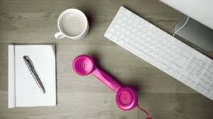 stock-footage-pink-phone-receiver-falling-onto-office-desk-beside-computer-coffee-and-notepadin-slow-motion